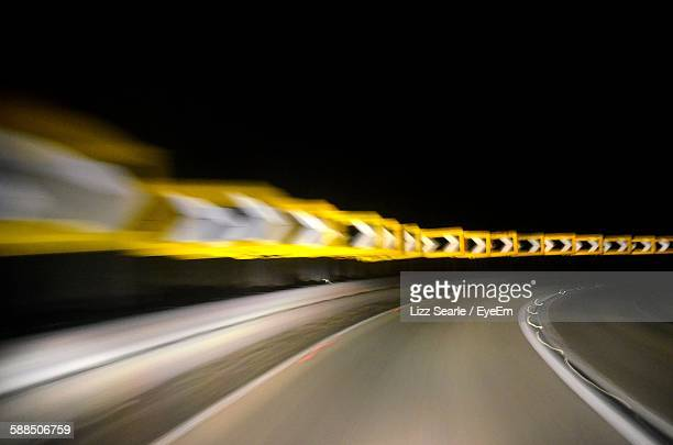 blurred image of illuminated street at night - curved arrows stock-fotos und bilder