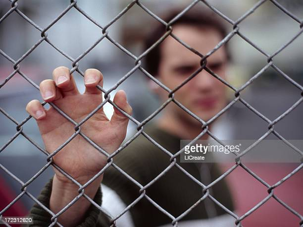 Blurred image of man holding the fence