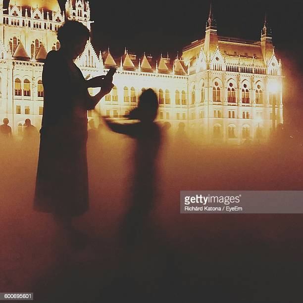 blurred image of mother and child on field against illuminated building - ハンガリー ストックフォトと画像