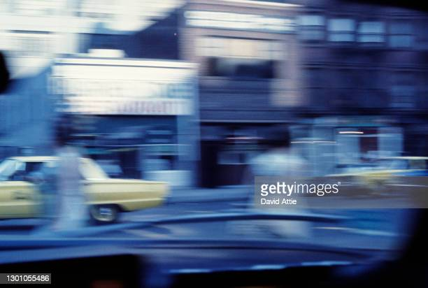 Blurred image of speeding taxicabs in front of the Blarney Stone in Midtown Manhattan in March 1962 in New York City, New York.