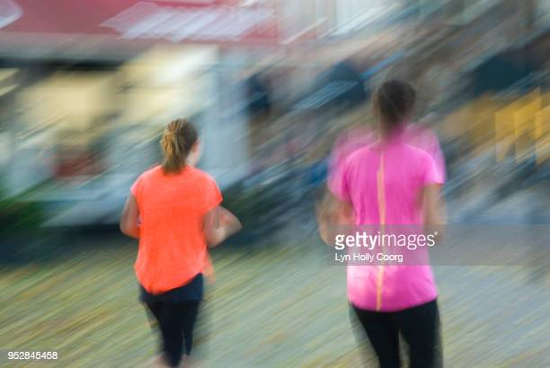 blurred image of two female joggers - lyn holly coorg stock pictures, royalty-free photos & images