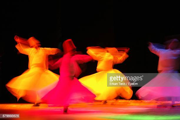 Blurred Image Of Whirling Dervishes Performing Against Black Background