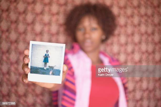 Blurred image of woman holding up old photograph