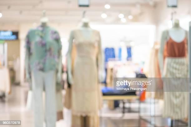 Blurred image of women clothes in clothing department. Defocused supermarket interior