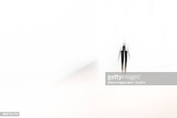 Blurred Man Walking Against White Background