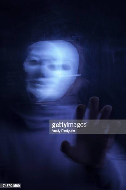 Blurred motion image of man wearing mask seen through glass
