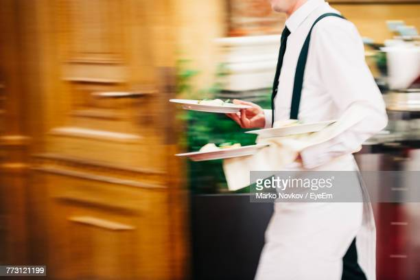 blurred motion midsection of man working at restaurant - waiter stock pictures, royalty-free photos & images