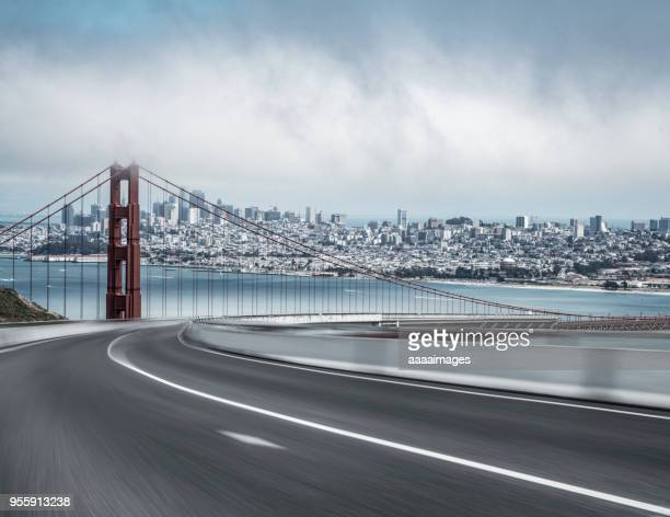 blurred motion motorway with san francisco skyline on background against cloudy sky - san francisco bridge fotografías e imágenes de stock