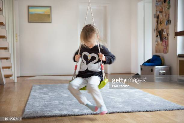 blurred motion of a child (6-7) playing on an indoor swing in a domestic hallway - nur kinder stock-fotos und bilder