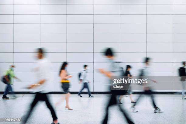 blurred motion of a crowd of busy commuters with protective face mask walking through platforms at subway station during office peak hours in the city - commuter stock pictures, royalty-free photos & images