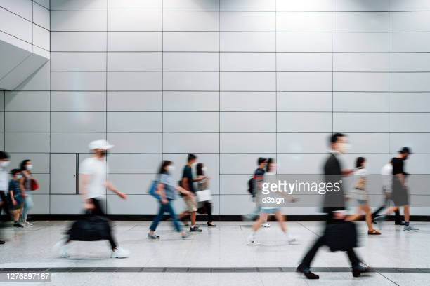 blurred motion of a crowd of busy commuters with protective face mask walking through platforms at subway station during office peak hours in the city - large group of people stock pictures, royalty-free photos & images