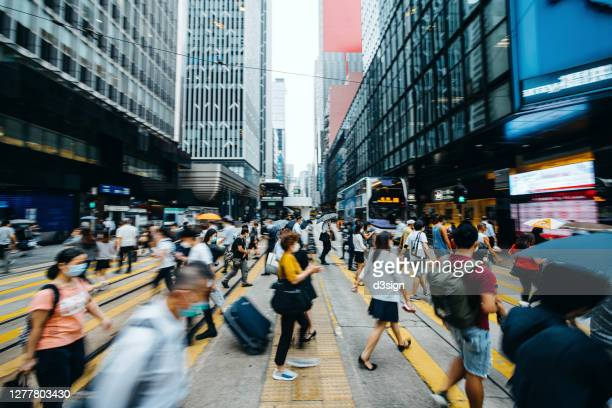 blurred motion of a crowd of busy commuters with protective face mask crossing the street in downtown financial district against contemporary corporate skyscrapers and city traffic during rush hour - prosperity stock pictures, royalty-free photos & images