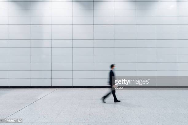 blurred motion of a male commuter with protective face mask walking through platforms at subway station alone in the city - underground station stock pictures, royalty-free photos & images