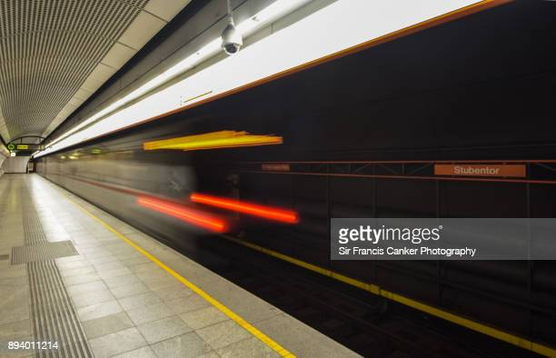 Blurred motion of a subway train departing Vienna's Stubentor metro station with an empty platform, Austria