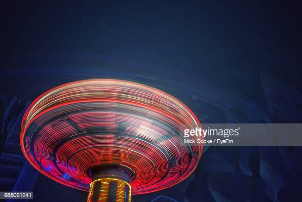 blurred motion of amusement park ride at night - turning stock pictures, royalty-free photos & images