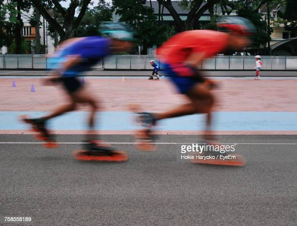 blurred motion of boys inline skating - inline skating stock pictures, royalty-free photos & images