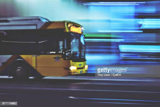 blurred motion of bus on road at night - autocarro imagens e fotografias de stock