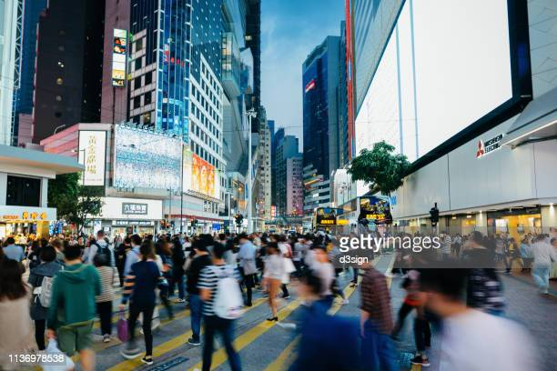 blurred motion of busy commuters crossing street in downtown district during office rush hours in the city - hong kong photos et images de collection