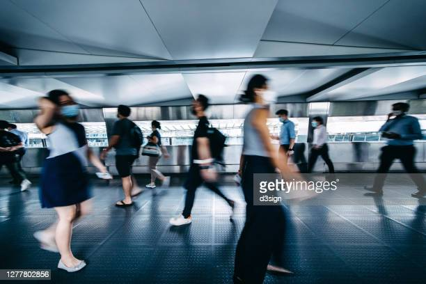 blurred motion of busy commuters with protective face mask walking on urban bridge in downtown district during rush hours in the city - central district hong kong stock pictures, royalty-free photos & images