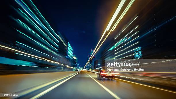 Blurred Motion Of Car Amidst Illuminated Buildings In City At Night