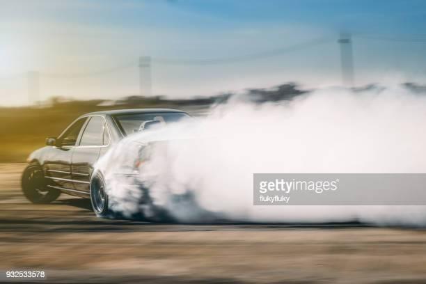 blurred motion of car emitting smoke against sky - landvoertuig stockfoto's en -beelden