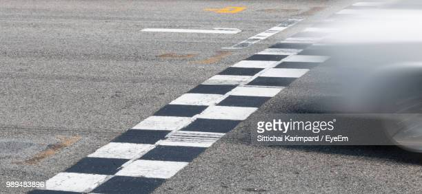 blurred motion of car moving on road - finish line stock pictures, royalty-free photos & images