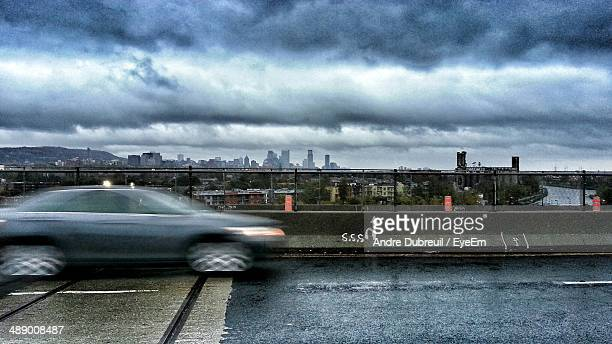 Blurred motion of car on road against cityscape