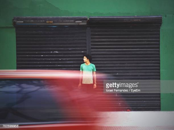 blurred motion of car on road against man standing on sidewalk - fast shutter speed stock photos and pictures