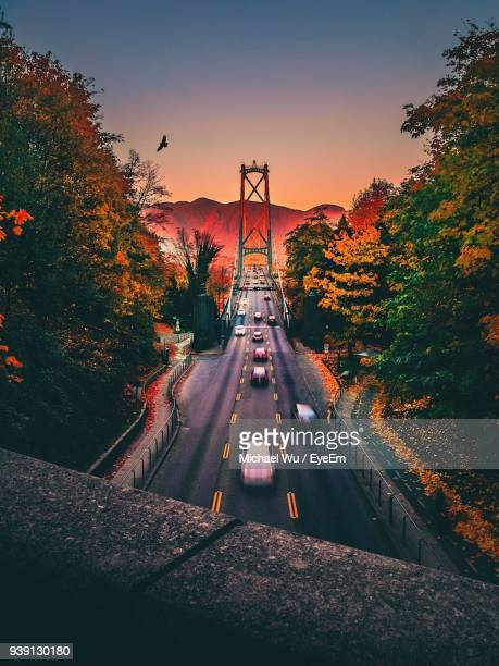 blurred motion of cars on suspension bridge during sunset - vancouver canada stock photos and pictures