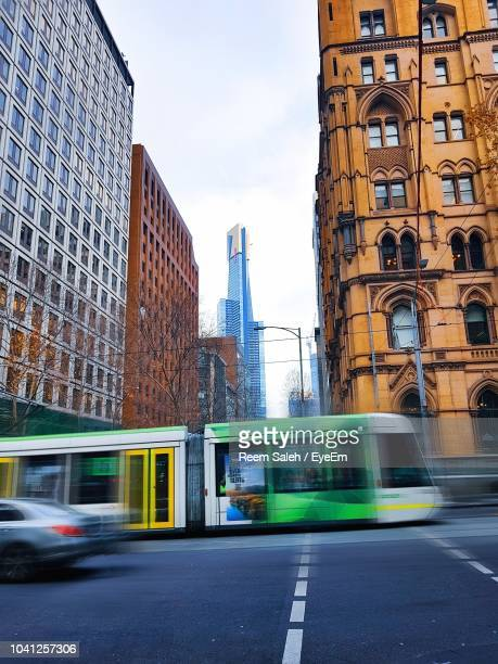blurred motion of city street and buildings against sky - tram stock photos and pictures