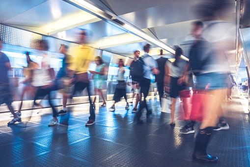 blurred motion of commuters walking through covered footbridge - gettyimageskorea