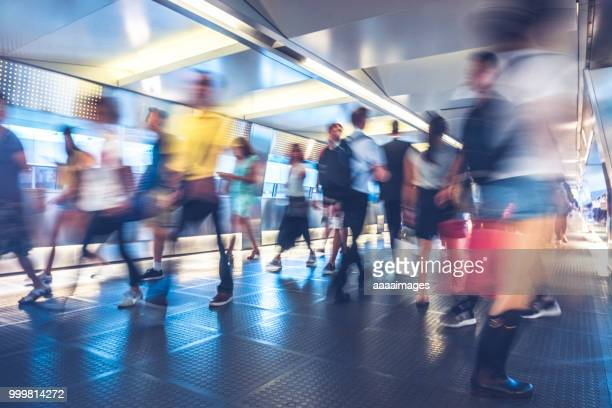 blurred motion of commuters walking through covered footbridge - footbridge stock photos and pictures