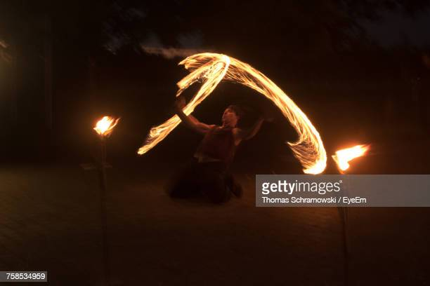 Blurred Motion Of Fire Dancer Performing At Night