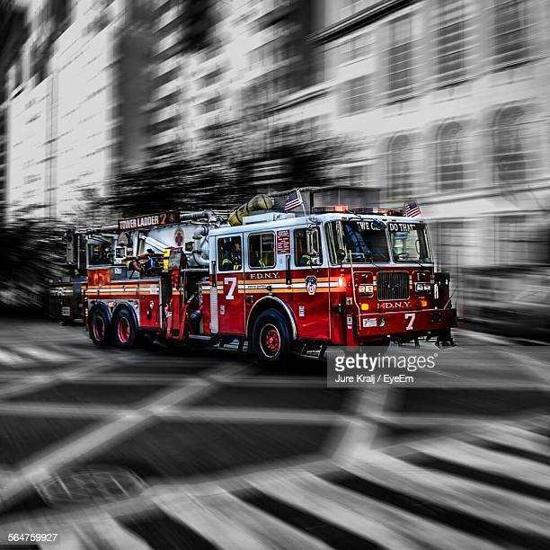 blurred motion of fire engine on road - firetruck stock photos and pictures