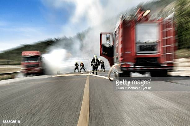 Blurred Motion Of Firefighters Spraying Water On Burning Truck
