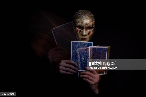 blurred motion of fortune teller holding tarot cards against black background - devin france photos et images de collection