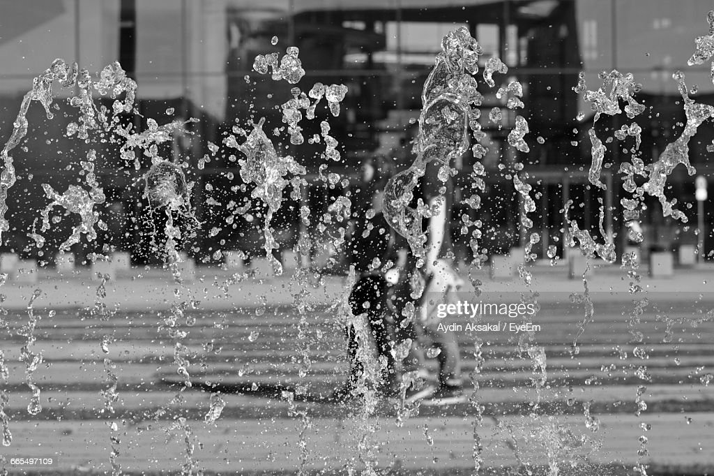 Blurred Motion Of Fountain Against Building : Stock Photo