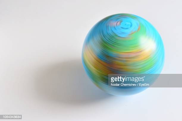 Blurred Motion Of Globe Spinning Over White Background