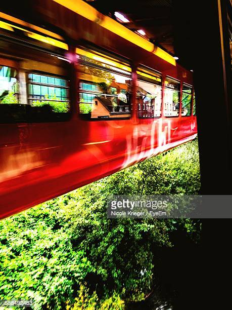Blurred Motion Of Hanging Monorail At Wuppertal Suspension Railway Against Green Trees
