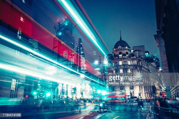 blurred motion of illuminated bus moving on road amidst buildings in city at night - illuminated stock pictures, royalty-free photos & images