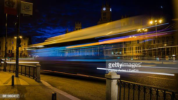 blurred motion of illuminated vehicle on street at night - carlos aviles stock pictures, royalty-free photos & images