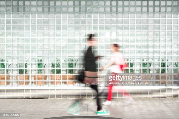 Blurred Motion Of Man And Woman Walking Against Building