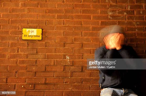blurred motion of man covering face against brick wall - see no evil hear no evil speak no evil stock pictures, royalty-free photos & images
