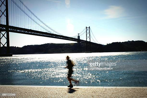 Blurred Motion Of Man Jogging By April 25Th Bridge Over Tagus River