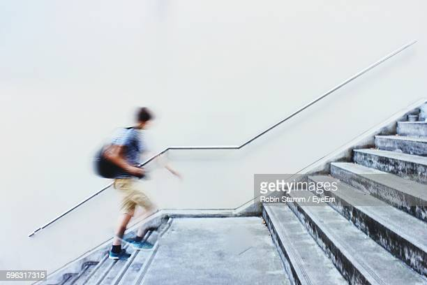 blurred motion of man moving up staircase - stairs stock photos and pictures