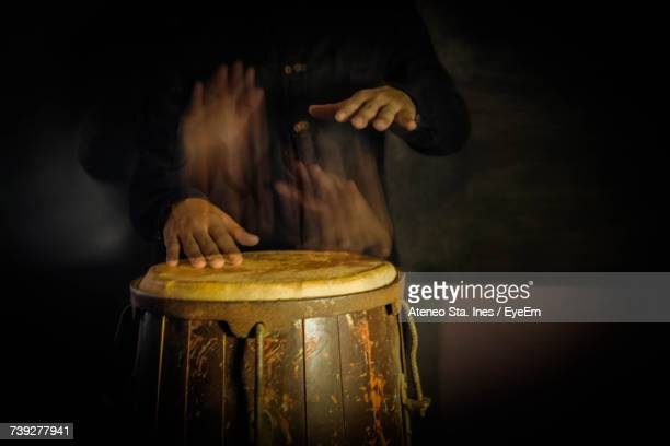 Blurred Motion Of Man Playing Conga In Darkroom