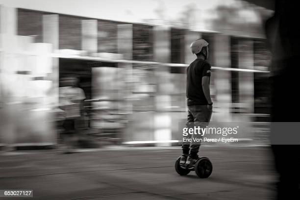 Blurred Motion Of Man Riding Electric Unicycle On Street