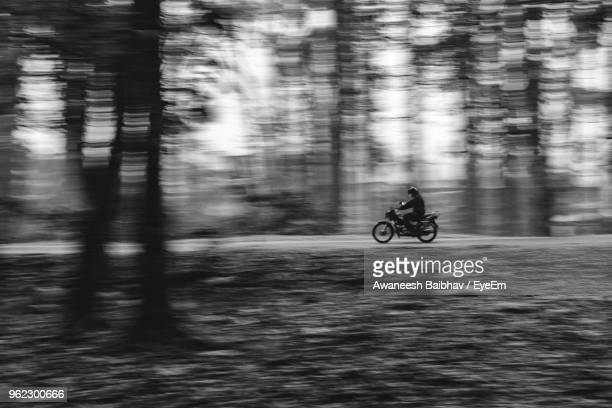 Blurred Motion Of Man Riding Motorcycle On Road In Forest