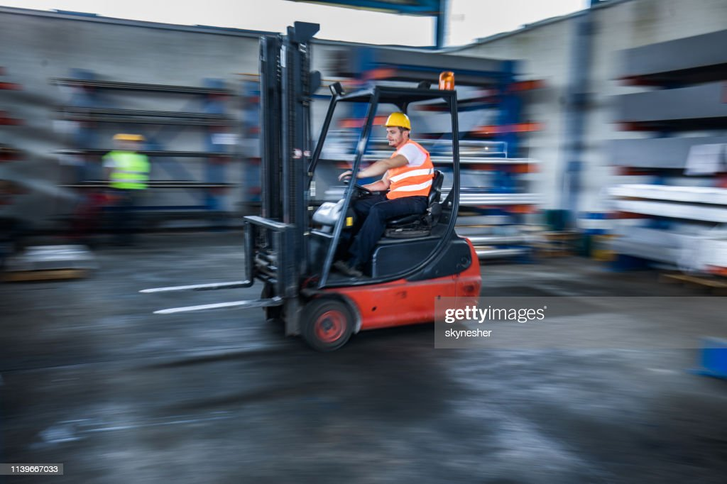 Blurred motion of manual worker in a forklift at warehouse. : Stock Photo