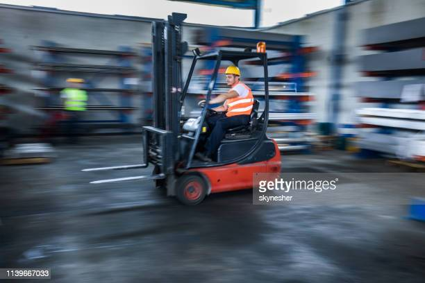 blurred motion of manual worker in a forklift at warehouse. - forklift stock pictures, royalty-free photos & images